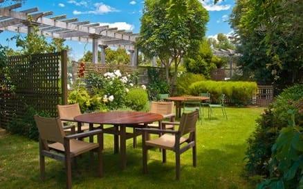 Sfeervolle tuin met veel groen en aparte zitjes.
